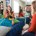 Band student playing instrument in residence room in company with others