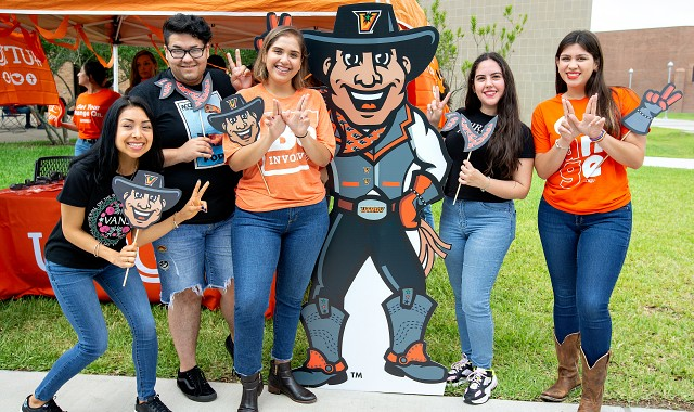 Students posing with Vaquero poster and displaying hand signs
