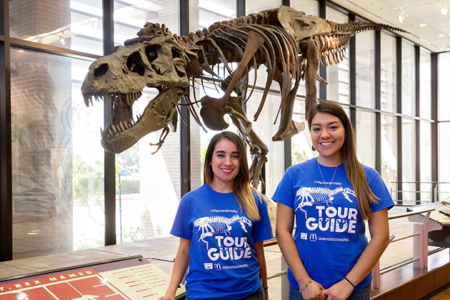 UTRGV student tour guides Valeria Salinas and Gabrielle Silva in front of Sue the Tyrannosaurus rex exhibit, following the press conference launch for the 15th anniversary of HESTEC 2016, on Thursday, Sep. 29, at the Visitors Center on the Edinburg Campus. (UTRGV Photo by Paul Chouy)