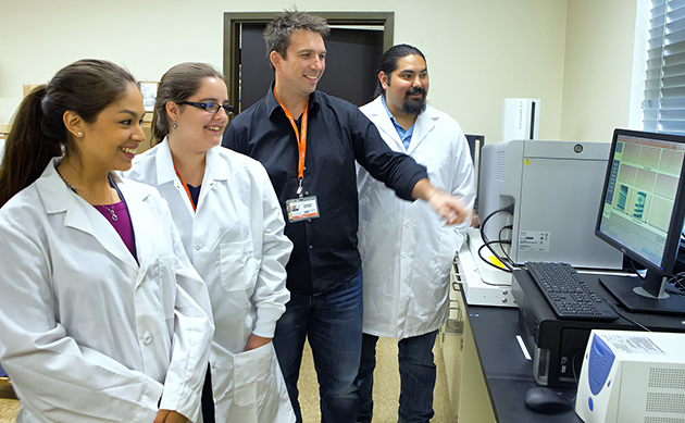 Samantha Gomez (at left), Cecilia Colom, and Johnathon Waggoner (far right) have landed gap-year jobs as research associates in the laboratory of Dr. Matthew Johnson (black shirt)