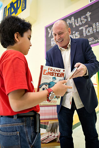 "Acclaimed children's author Jon Scieszka gave out copies of his book, ""Frank Einstein and the Antimatter Motor,"" to students at Emiliano Zapata Elementary School in Mission on Friday, March 4, during UTRGV's annual FESTIBA week. The author and students were part of the Reading Rock Stars program, organized by the Texas Book Festival. UTRGV's FESTIBA event (UTRGV photo by Paul Chouy)"