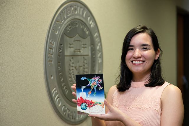 UTRGV finance student Selene Salinas Elizondo, seen here at the UTRGV President's Office on the Edinburg Campus, displays her winning design.