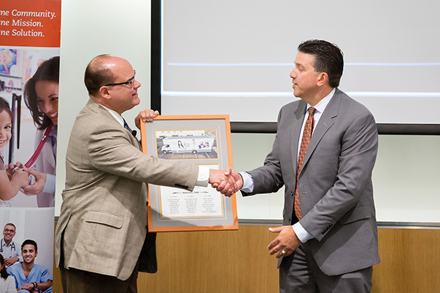 Dr. John Krouse (at left), dean of the UTRGV School of Medicine and vice president for Health Affairs, and Dave Milich, CEO of UnitedHealthcare Texas/Oklahoma, exchanged plaques during an event on Thursday, Sept. 28, 2017, at the Medical Education Building on the UTRGV Edinburg Campus. The event was to celebrate the partnership between the UTRGV School of Medicine and the United Health Foundation that helped bring about the Unimóvil mobile clinic (UTRGV Photo by Paul Chouy)