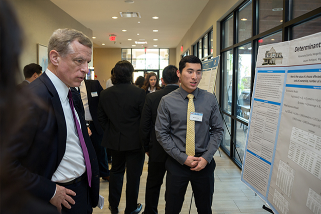 UTRGV student Brandon Lau talks about his group's research project with Robert Kaplan, president and CEO of the Federal Reserve Bank of Dallas, during the Border Economic Development and Entrepreneurship Symposium (BEDES) hosted by UTRGV, the Federal Reserve Bank of Dallas-San Antonio Branch, and the McAllen Chamber of Commerce. The symposium was held Friday, Dec. 1, at the Embassy Suites in McAllen. (UTRGV Photo by Paul Chouy)
