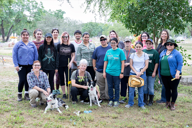 Dr. Sarah Rowe (kneeling, far left), UTRGV assistant professor of sociology and anthropology, is seen here with search specialists from the Institute for Canine Forensics Lynne Engelbert (kneeling, at right) and Adela Morris (back row, fourth from left), along with search dogs Jasper and Piper and UTRGV students in Rowe's service learning class, all of whom are helping to identify burial sites at the abandoned Hidalgo County Pauper Cemetery. The cemetery closed in the early 1990s, leaving many graves unmarked and many identification records lost or abandoned. (UTRGV Photo by Paul Chouy)