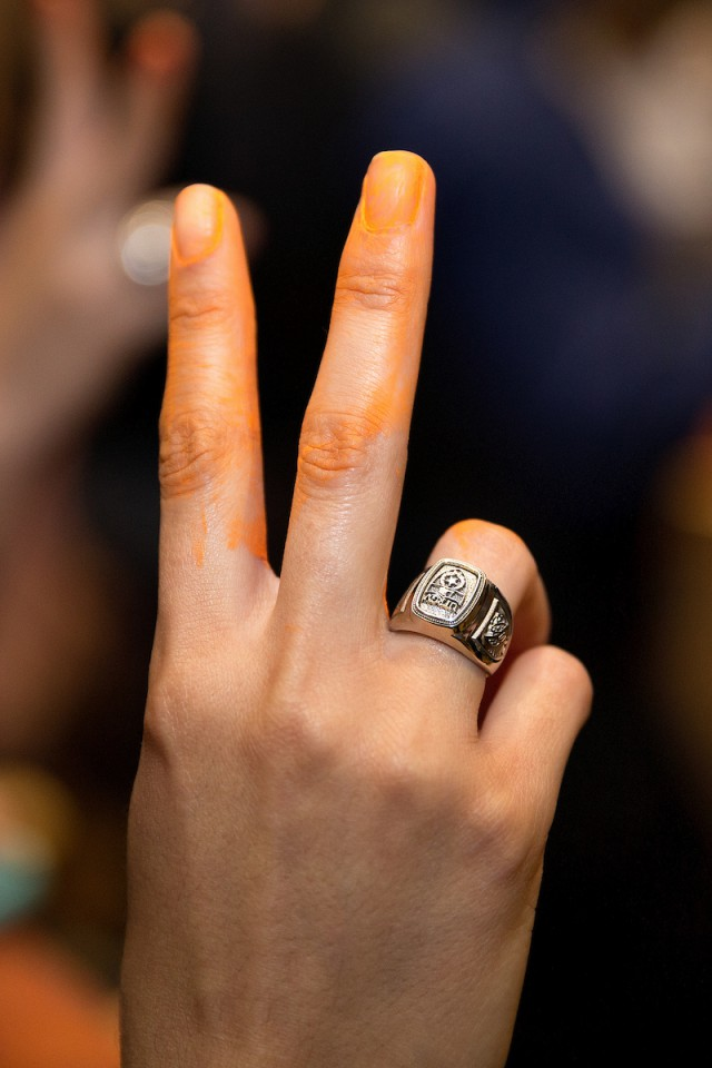 "A UTRGV student displays the new UTRGV class ring and the results of the ceremonial ""V-Dunk,"" in which students dip their right index and middle fingers into orange dye and create an orange ""V,"" the Vaqueros sign. (UTRGV Photo by Paul Chouy)"