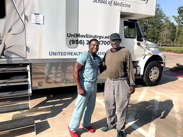 Dr. Charles Lewis (at left), a family medicine resident with the UTRGV Family Medicine Residency Program at Doctors Hospital at Renaissance, poses with a Houston-area resident outside the UTRGV School of Medicine's mobile clinic, Unimóvil.