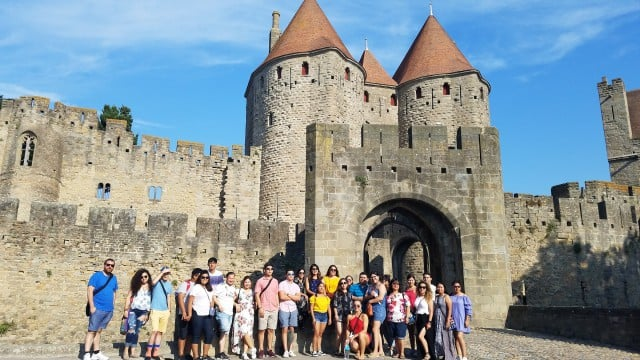 A group of UTRGV students in Europe standing in front of a castle