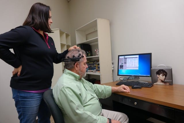 The UTRGV Department of Marketing, in the Robert C. Vackar College of Business and Entrepreneurship, is expanding its consumer neuroscience research with advanced techniques like eye trackers and electroencephalograms to register brainwaves. Here, Zoila Zambrano, a UTRGV doctoral candidate in marketing, sets up the EEG for a demonstration, with Dr. Michael Minor, professor and chair of the marketing department, who is spearheading the research. (UTRGV Photo by Malena Hernandez)