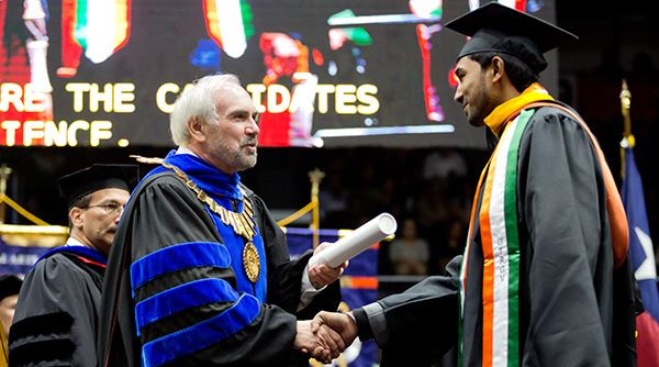UTRGV president Guy Bailey shaking a student's hand at graduation