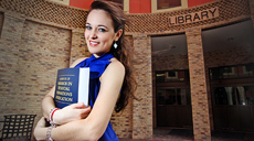 A smiling UTRGV student holding a book in front of the UTRGV library