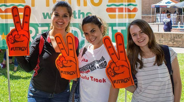 UTRGV students holding V's up foam hands.